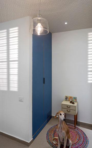 במבואה עומדת שידה ועליה שלושה ציורים מיניאטוריים. לידה יש נישה שמתפקדת כארון ושנסגרה בדלתות כחולות (צילום: שי אפשטיין)