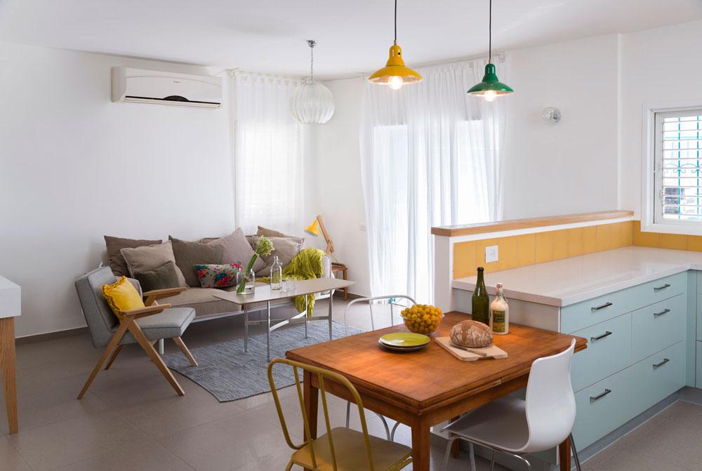 המטבח כולל ארונות תחתונים מפורמייקה בצבע ''אקווה'' ומשטח אבן קיסר לבן. אריחים בצבע חרדל מכסים את הקיר. במרכז המטבח הוצב שולחן אוכל מעץ, ומעליו שתי מנורות מפח. משמאל: הסלון, ובו ספה בגוון חול, כורסה שרופדה בגוון אפור-תכלת ושולחן קפה שהורכב מפלטת פורמייקה ומרגליים ממוחזרות (צילום: שי אפשטיין)