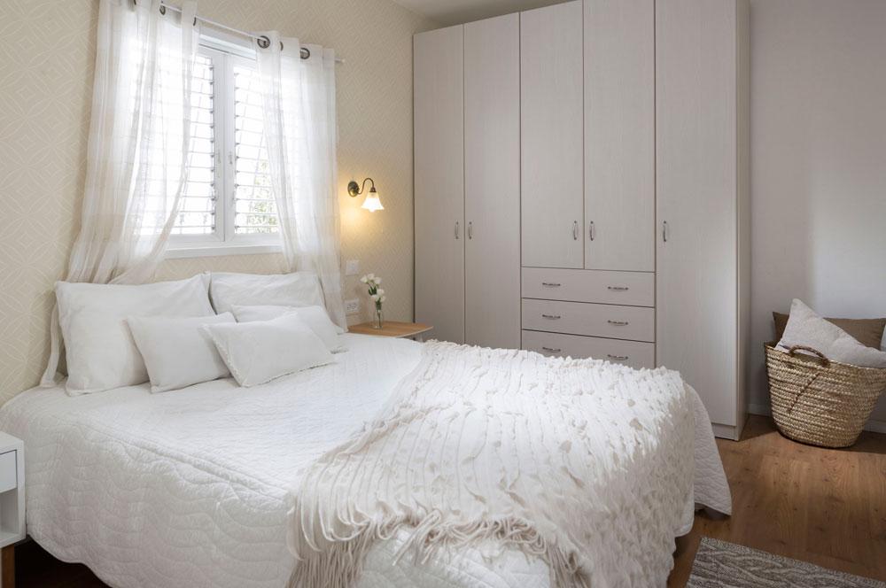 חדר ההורים עוצב בגוונים טבעיים ובהירים: את הרצפה מכסה פרקט אלון והמיטה נשענת אל קיר שעליו טפט בדוגמה זהה לזה שהודבק במסדרון, בגוון חול. הארון הפשוט הובא מהדירה הקודמת (צילום: שי אפשטיין)