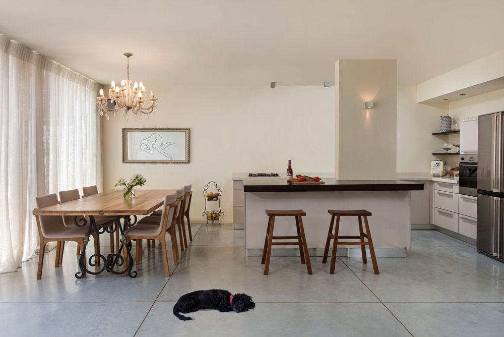 עיקר השיפוץ נעשה בקומת השינה, לא בקומת הכניסה. המטבח נותר כשהיה, שכן הוא עבר שיפוץ יסודי לפני כמה שנים. במראה שבפינת האוכל משתקפת דמות האשה שמקשטת את קיר הסלון (צילום: אביב קורט)