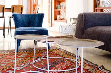 על שטיח קילים הוצבו שולחנות המורכבים ממגשים פרסיים על רגלי ברזל שנצבעו בלבן (באדיבות סטודיו Other:wise)
