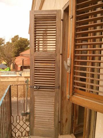 """התריסים """"לפני"""", במרפסת הסלון הקטנה. דהויים ומתקלפים (צילום: רועי קדרנל, באדיבות סטודיו Other:wise)"""