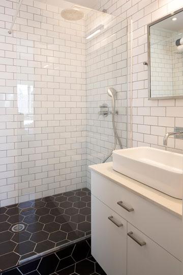 חדר הרחצה של ההורים. אריחים משושים שחורים על הרצפה, ולבנים מלבניים על הקירות (צילום: שי אפשטיין)