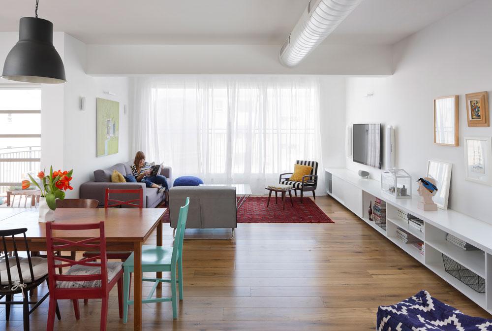 """השטיח מאמא שלו, הספות עברו מהדירה בתל אביב, שולחן הקפה מ''טולמנ'ס'', פוף אחד מ""""ביתילי"""" והשני מעשי ידיה של אמא שלה. את כורסת הפסים מצאה בעלת הבית ברחוב וריפדה מחדש (צילום: שי אפשטיין)"""