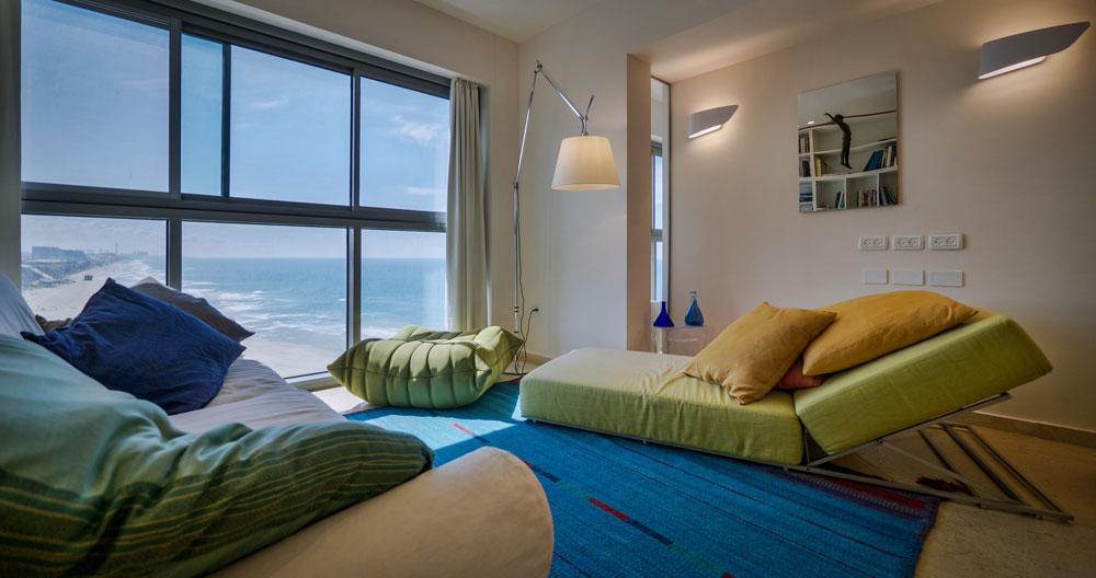 הסלון והמרפסת. מאחר שאין סיבה להתחרות בנוף הים, שהוא הנכס האמיתי של הדירה, פורקו קטעי קירות כדי לא להסתיר את המים והחול (צילום: איתי סיקולסקי)