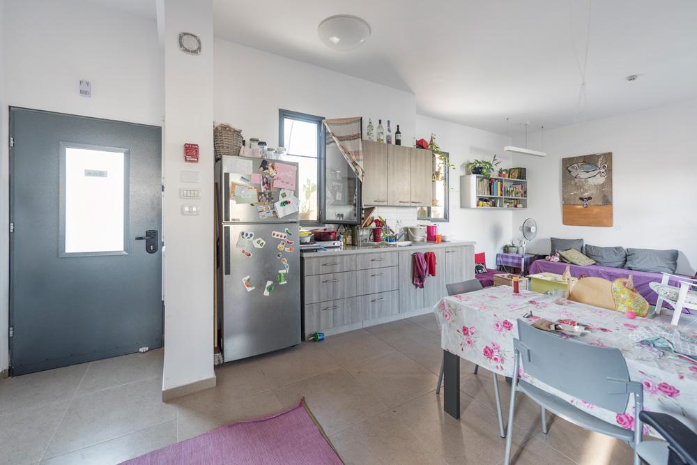 דלת הכניסה (משמאל), המטבח, פינת האוכל והסלון. החלונות תוכננו לפי עיקרון קפדני: בחדרים הדרומיים הם בגודל של 18% משטח החדר, וגודלם בחדרים הצפוניים הוא עד 10% מהשטח (צילום: אלי סינגלובסקי)
