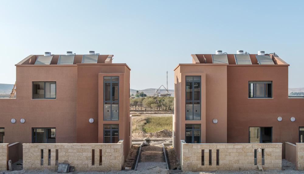 """החזית הדרומית של שניים מהבתים שעדיין לא הושלמו. החלונות הצרים הם של הסלון, ואילו הרחבים יותר הם """"חלונות חממה"""" של חדרי השינה (צילום: אלי סינגלובסקי)"""