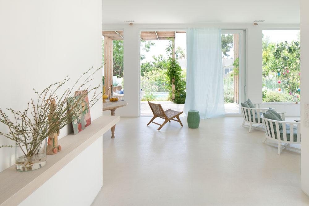 המראה מדלת הכניסה לכיוון הסלון והגינה האחורית. קומת הכניסה רוצפה באריחי ליימסטון גדולים, ובכך הושלם הרקע הלבן - קירות, תקרה ורצפה. משמאל: קובייה שמסתירה מעלית (צילום: עמית גרון)