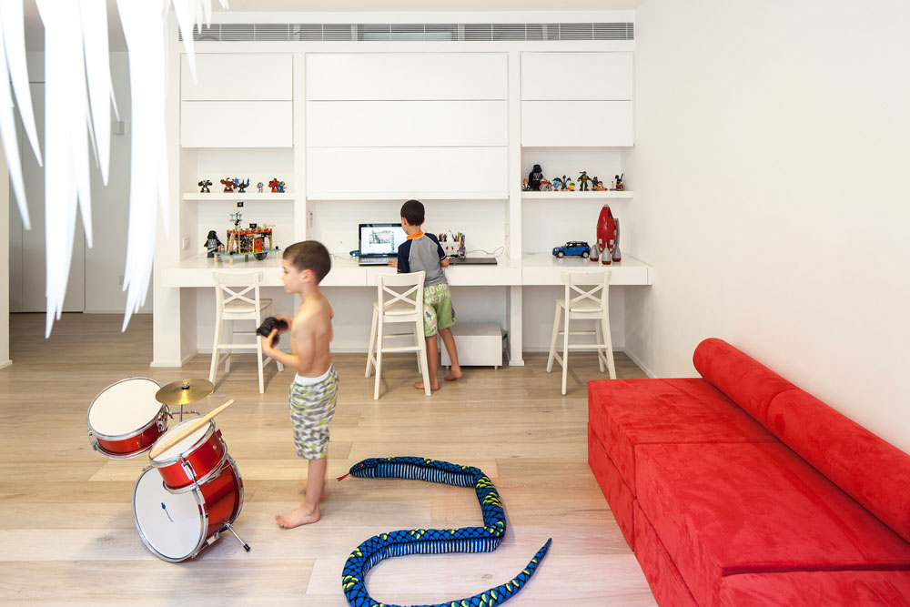 חלל המשחקים לילדים, שנמצא במרתף, כולל ספרייה שתוכננה במיוחד והוזמנה מנגר ופינת ישיבה המרופדת בבד קורדרוי אדום. במרתף יש גם חדר עבודה וכושר של בעל הבית (צילום: עמית גרון)