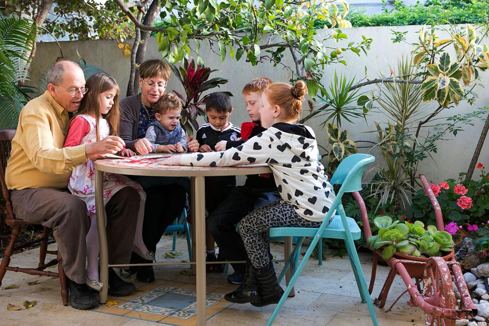 """ניצה ומיכאל זלטקין עם חמשת נכדיהם בחצר ביתם בהרצליה. שטח הבית הוא 160 מ""""ר על מגרש של 300 מ""""ר. יש בו שתי קומות, אבל רק התחתונה שופצה (צילום: שירן כרמל)"""