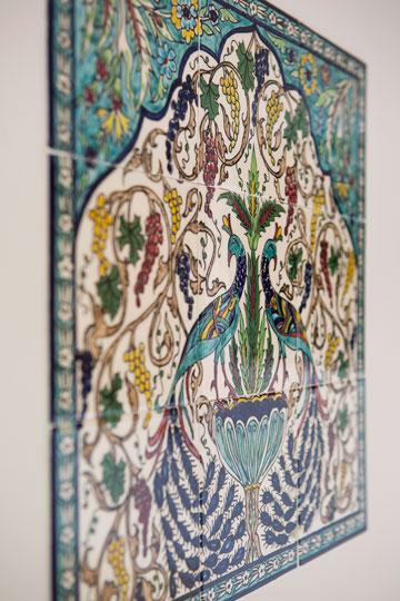 בשירותי האורחים בולטת תמונת טווסים שמורכבת מ-9 אריחים ארמניים שנקנו בבית המלאכה של משפחת בליאן במזרח ירושלים לפני כ-30 שנה (צילום: שירן כרמל)