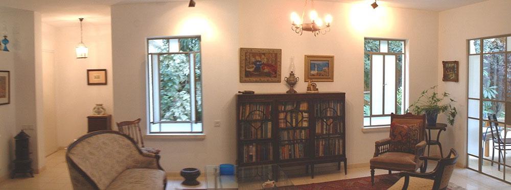 """הסלון """"לפני"""". המזנון ושתי יצירות האמנות שתלויות מעליו נשארו, אבל שינו מקום. חלק מהכורסאות רופדו מחדש"""