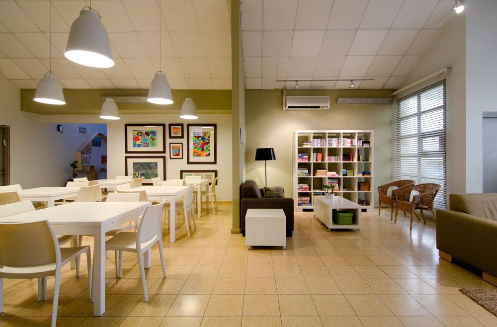 אור נעים, וילונות, תמונות על הקירות וכוורת ספרים. פחות מוסד, יותר בית (צילום: אילן נחום)
