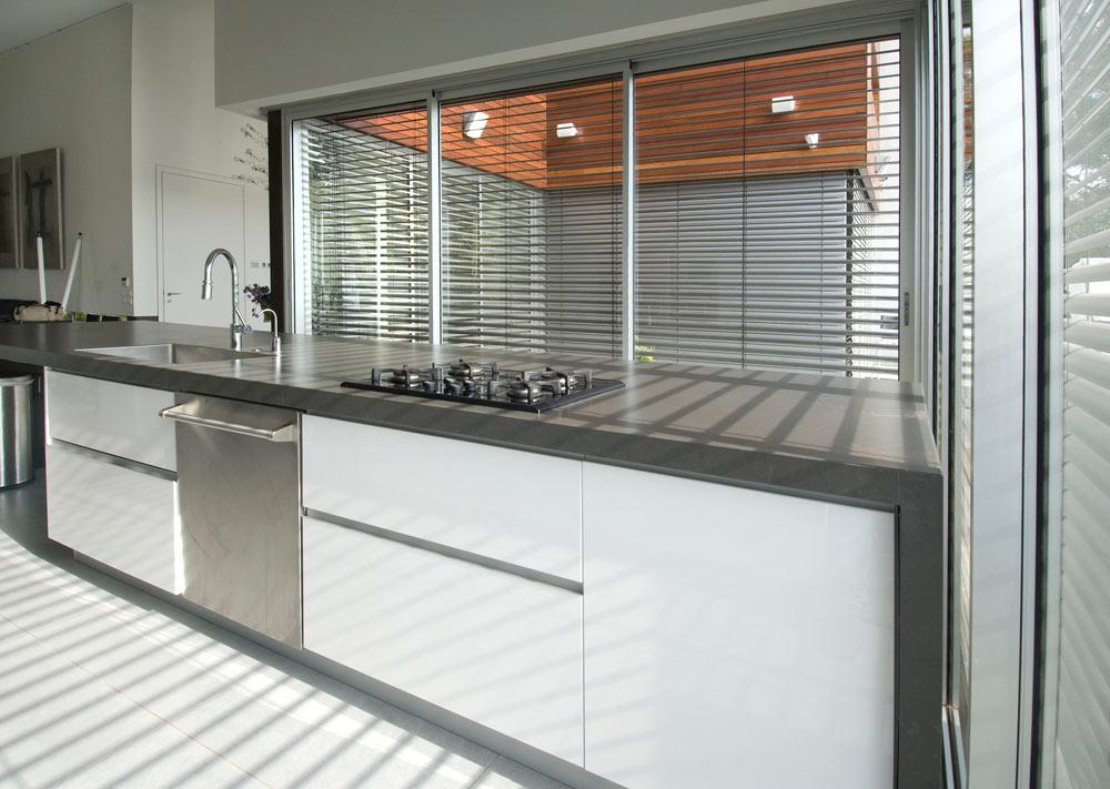 משטח ה''אי'' במטבח עשוי בטון, הארונות צבועים בצבע הקיר הלבן ודלתות מכשירי עשויות נירוסטה, במראה תעשייתי במכוון (צילום: עמרי מירון)