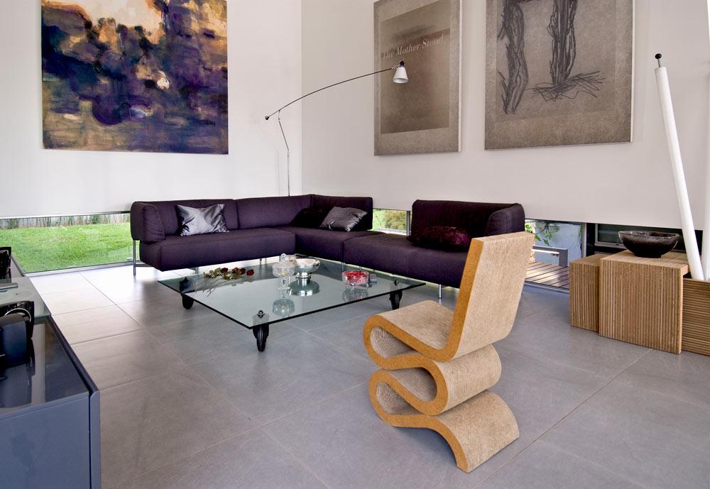 גם הפריטים נבחרו בקפידה: כיסא מקרטון בעיצוב פרנק גרי, למשל, בולט בסלון. התאורה שקועה בתקרה ושתי מנורות עומדות משלימות אותה, ללא מנורות תלויות (צילום: עמרי מירון)