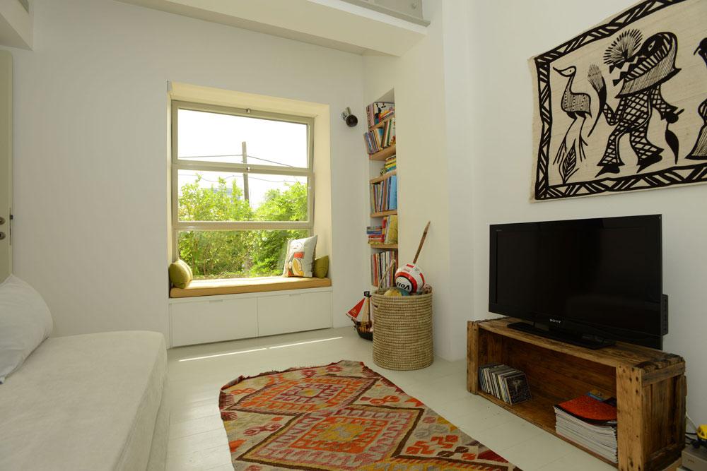 ובחזרה לקומת הקרקע: חדר המשפחה גם הוא מלא אור ומעוצב מחומרים פשוטים, עם ספסל ישיבה מתחת לחלון גדול (צילום: רמי חכם)