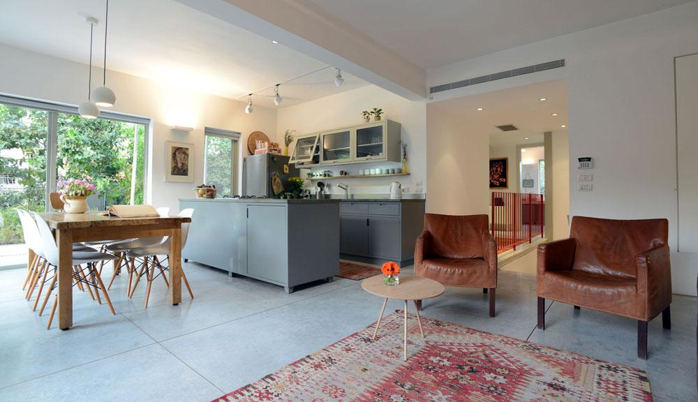 ארונות המטבח, ''אי'' העבודה ופינת האוכל תוכננו כשלושה קווים מקבילים. מסדרון מוביל מהסלון לחדרי הילדים והמשפחה, ומעקה אדום מוסיף קלילות (צילום: רמי חכם)