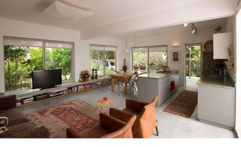 מבפנים התחושה היא של בית פרטי: הצמחייה נראית מכל החלונות הגדולים. צבעי הרקע נייטרליים - אפורים-ירוקים - והרהיטים בצבעים חמים. לאורך כל הקיר החיצוני נבנה ספסל בטון שימושי ונוח (צילום: רמי חכם)