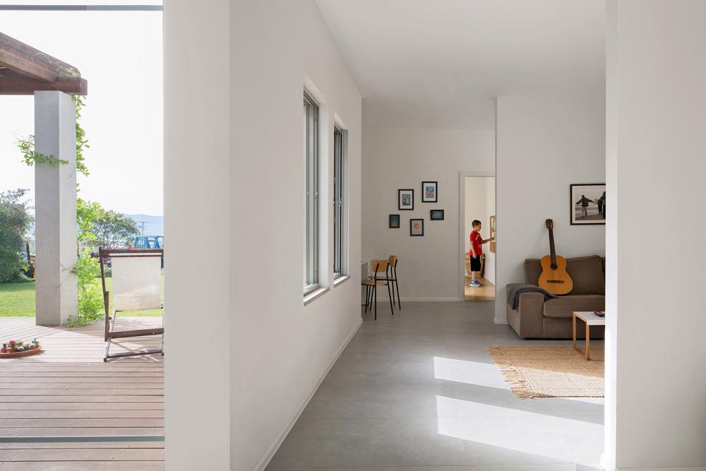 מבט מהמסדרון אל פינת המשפחה והעבודה, שמפרידה בין יחידת ההורים לחדרי הילדים. הבית נראה ממבט על כאות הלועזית L, תוחם את המגרש (צילום: שי אפשטיין)