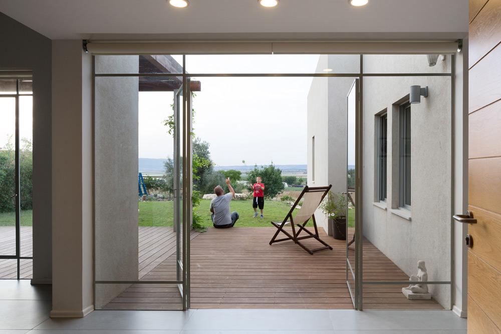 מבט מדלת הכניסה דרך המבואה הישר אל הגינה ונוף השדות. משמאל למבואה חלל פתוח שבו הסלון, פינת האוכל והמטבח, ומימינה חדרי השינה (צילום: שי אפשטיין)
