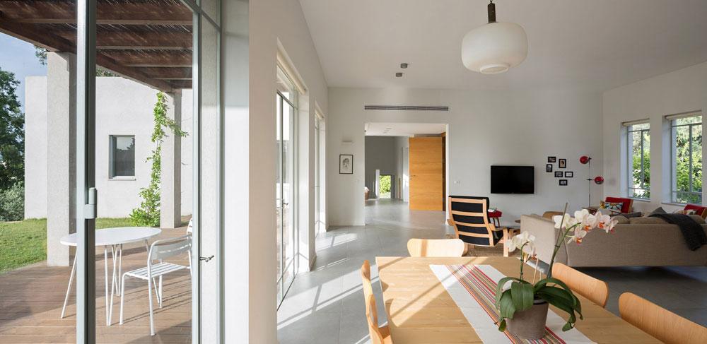 מבט מהמטבח אל דלת הכניסה והלאה: בסוף המסדרון המדרגות היורדות אל הקומה התחתונה. מימין יחידת ההורים, שבה מובילה פינת עבודה אל חדר השינה, כדי להבטיח פרטיות מרבית (צילום: שי אפשטיין)