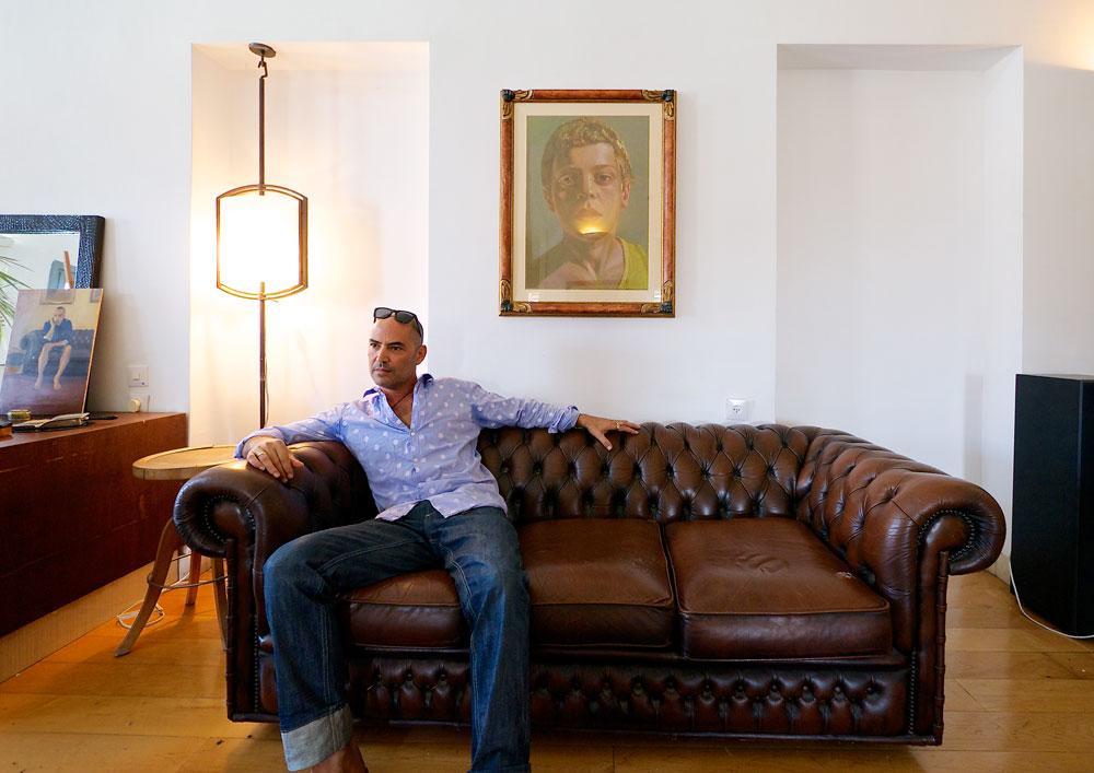 """ויקטור (ויוי) בלאיש בביתו בשכונה המרונית ביפו. """"הבית הוא סוג של מקלט מן החוץ, לכן היה חשוב לי שישדר חום, נוחות ופרקטיקה"""" (צילום: איתי סיקולסקי)"""