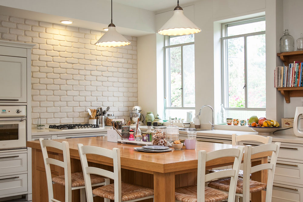 המטבח בסגנון כפרי, עם ארונות שדלתותיהן ממוסגרות, קיר לבנים צבוע לבן, ''אי'' לאחסון וארוחות יומיומיות ומעל הכיור שני חלונות גדולים, שפונים אל הפרגולה שבחוץ (צילום: שירן כרמל )