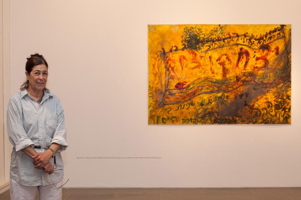 נעמי גבעון לצד ציור של משה גרשוני. את כל האמנים שעבודותיהם תלויות בבית היא הכירה או מכירה היטב. חללי התצוגה פתוחים לציבור ללא מטרות רווח (צילום: טל ניסים)