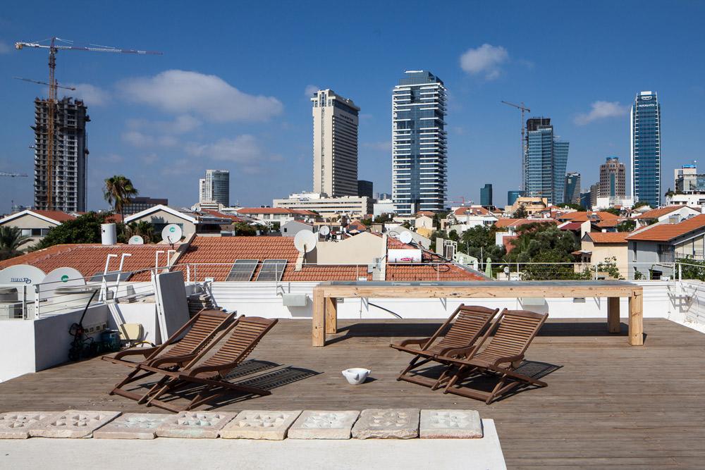 מגג הבית אפשר להשקיף על גגות השכונה והמגדלים שמקיפים את נוה צדק כמעט מכל כיוון. גבעון קנתה בית היסטורי שעמד נטוש 30 שנה, משום שאהבה את מקצב החלונות בקירותיו (צילום: טל ניסים)