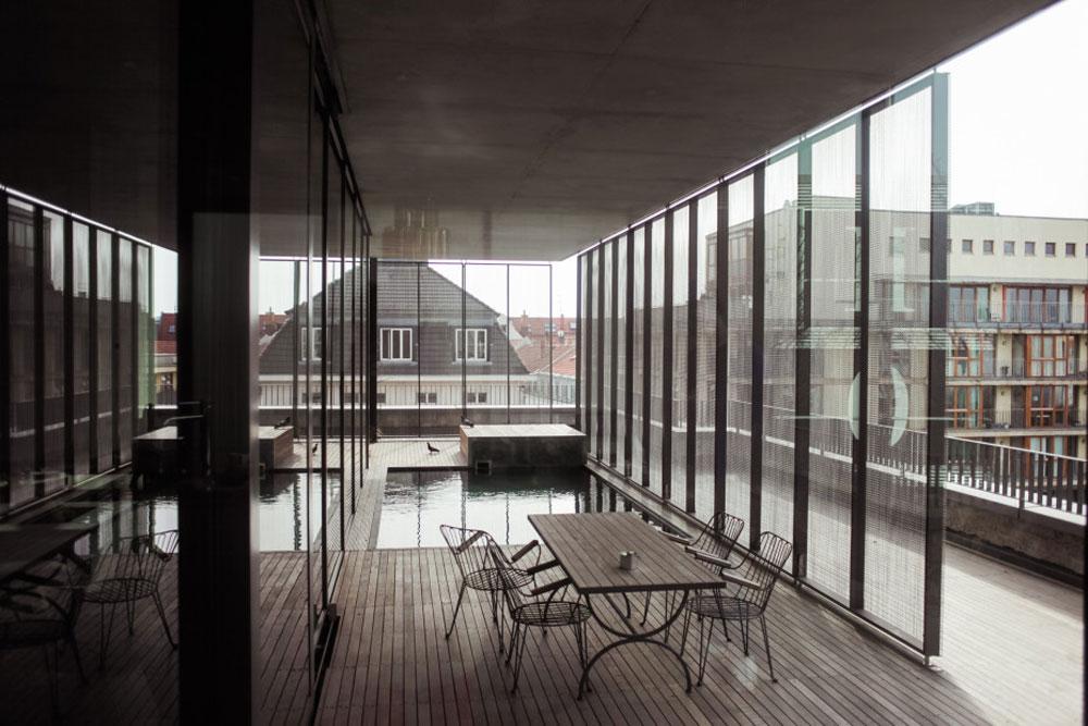 גגות השכונה ניבטים מבעד לקירות הזכוכית של הפנטהאוז, ואין זכר לגוש הבטון שעליו הדירה מונחת (צילום: Ailine Liefeld for Freunde von Freunden)