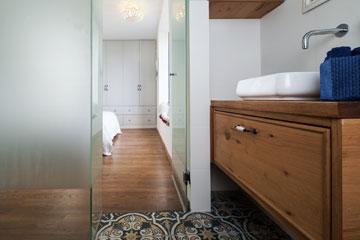 חדר הרחצה של ההורים. הרצפה חופתה באריחים מעוטרים בגוני כחול. כיור הונח על ארון מרחף מעץ אלון. הברז יוצא מהקיר (צילום: טל ניסים)