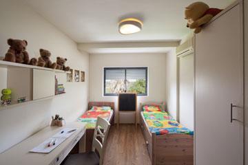 חדר הבנים: שתי מיטות, ארון בגדים ושולחן עבודה בצבע שמנת עם ספרייה תלויה (צילום: טל ניסים)
