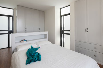 חדר הארונות שהיה ליד חדר ההורים בוטל, ובמקומו נבנו שני ארונות בגדים, שלו ושלה. דלתות מאלומיניום אפור מובילות למרפסת (צילום: טל ניסים)