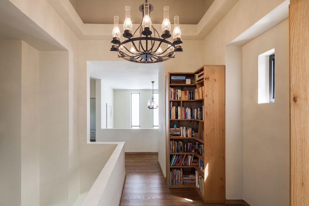בקומת חדרי השינה לא שונתה חלוקת החדרים, אבל נעשו בה שינויים. למשל, ה''גשר'' שמוביל לחדר ההורים חופה בפרקט, מעקה הזכוכית הוסר, שטח הרצפה הורחב והוצבה בו ספריית עץ (צילום: טל ניסים)