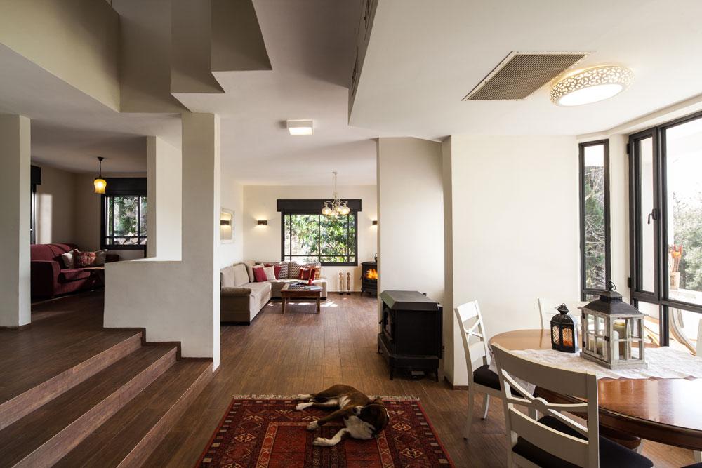 מבט מכיוון המטבח. במעלה המדרגות משמאל ניתן לראות את חדר המשפחה. רהיטי פינת האוכל, כולל השטיח, הובאו מהבית הקודם. בסלון ספה פינתית בצבע טבעי ושולחן קפה, שהוצבו מול דלת הזכוכית שמובילה החוצה. שלוש מדרגות מפרידות בין מפלס הכניסה למפלס הסלון והמטבח (צילום: טל ניסים)