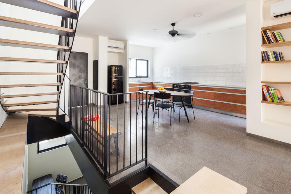 קירות המטבח כוסו באריחים לבנים ופשוטים, משטח העבודה עשוי פלטות בטון מיובאות, שהותקנו בידי בעלי הבית. המדפים בסלון נחתכו מאותו עץ סנדוויץ' פשוט, שממנו עשויות המדרגות (צילום: טל ניסים)