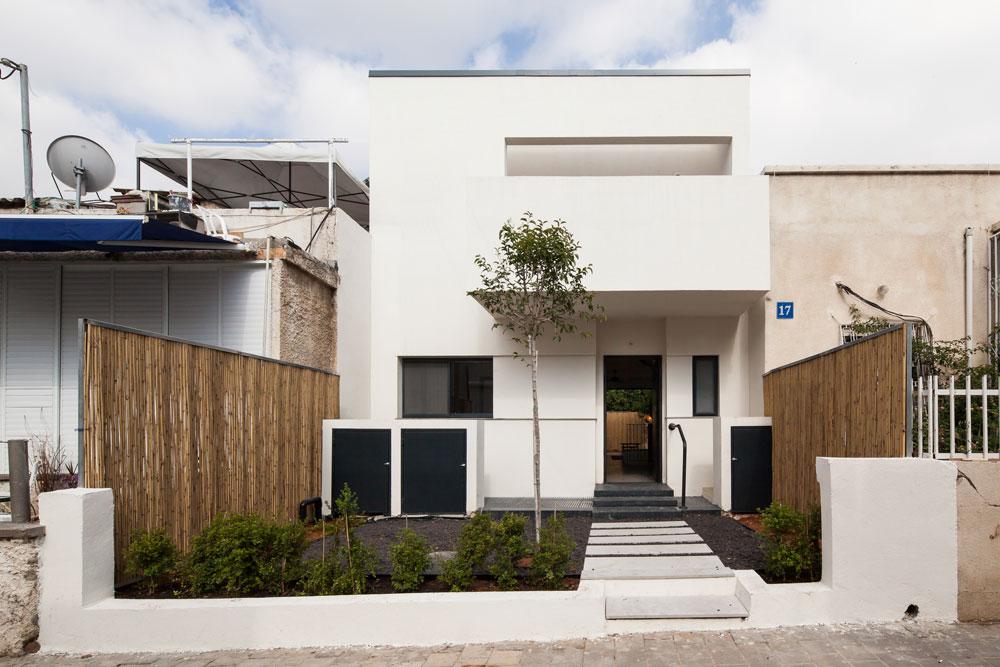 כך נראה הבית מלפנים: צמוד לשני שכניו, בסגנון האופייני לשכונה. בקומה העליונה מרפסת גדולה שפונה לחזית. כבר בכניסה ניכרת הבחירה בחומרים גולמיים, פשוטים: מדרכי בטון ודלת ברזל (צילום: טל ניסים)