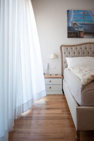 חדר ההורים חופה בפרקט עץ אלון. המיטה היא מעץ בגוון טבעי עם ראש מרופד בבד פשתן אפור בטכניקת קפיטונאז' (צילום: גלעד ארדט)
