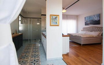 קיר שמנותק מהתקרה מפריד בין אזור השינה (מימין) לאזור הרחצה (משמאל) בחדר ההורים (צילום: גלעד ארדט)