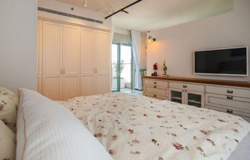 משמאל למיטה ניצב ארון בגוון שמנת. ממול, שידה עם גלגלים, ומעליה טלוויזיה. מתזי המים שבתקרה נצבעו בשחור (צילום: גלעד ארדט)