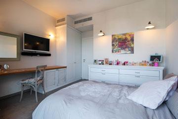חדר הבת: מיטה, שידה שנצבעה בלבן, מדף שמשמש כשולחן עבודה ואיפור, מתחתיו ארונית, למעלה טלוויזיה וראי (צילום: גלעד ארדט)