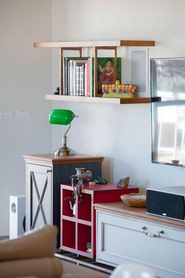 חלק נוסף של המזנון שבסלון. מעל הארוניות תלויים מדפים מעץ גושני שחוברו זה לזה בעזרת מסגרות מפליז (צילום: גלעד ארדט)