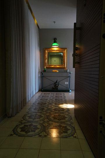 """מבואת הכניסה מעוטרת ב""""שטיח"""" מאריחים. משמאל, ארון שהוסתר על ידי וילון. מול הדלת, שידה ומעליה מראה במסגרת זהב (צילום: אמיר גולן)"""