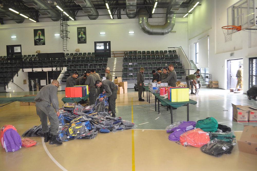 חיילים עוזרים לסדר את ציוד הלימוד שהגיע לעמותה בשנה שעברה