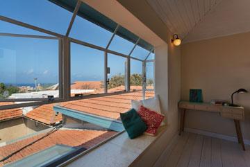 """חדר השינה של בלינדר: המיטה מ""""איקאה"""", השולחן משוק הפשפשים, החלון ''נדחף'' החוצה, כדי ליצור ספסל שמשקיף אל הנוף (צילום: אסף פינצ'וק)"""