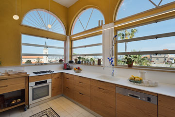 חלונות המטבח הוחזרו בשיפוץ לגודלם המקורי, ונבנו פרופילי ברזל חדשים. הצבעים חמים (צילום: אסף פינצ'וק)