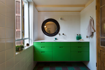 חדר הרחצה שלצד הסלון. הארונות ירוקים, הרצפה היא בגוונים ירוק וחום-סגלגל, המראה מוסגרה במקלעות קש (צילום: אסף פינצ'וק)
