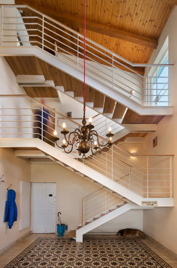 """גרם המדרגות, שעליו תלוי השלט """"מועדון הקצינים"""", שמוביל לסלון. מנורת הפליז משתלשלת בעזרת חבל אדום (צילום: אסף פינצ'וק)"""