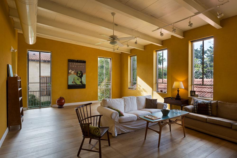 """כמו המטבח, גם הסלון נצבע בצהוב חלמוני חם. הרצפה חופתה בפרקט ואת הרהיטים אספה בלינדר במרוצת השנים. התקרה פורקה ונבנתה מחדש עם חיזוקים בפרופילי """"איי"""". הרעיון לרכוש בית גדול קסם לבלינדר, מכיוון שהיא מרבה לארח את בני משפחתה. כדי להתמודד עם ההוצאות, היא משכירה את הקומה השנייה לשותפים שחולקים איתה את הסלון והמטבח (צילום: אסף פינצ'וק)"""