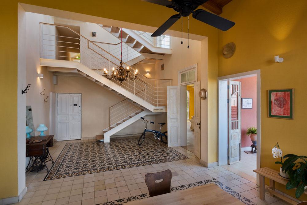 """קומת הכניסה היא החלק המרכזי בדירה. גודלה 120 מ""""ר, והיא מתנשאת לגובה של שלושה מפלסים: התקרה המשופעת מיתמרת בשיא גובהה לשבעה מטרים ו-30 ס""""מ, ובאזור הנמוך היא מגיעה לשישה מטרים """"בלבד"""". הדלת הראשונה מימין מובילה למרפסת, וזו שקרובה למדרגות מובילה לסלון (על אף שהשלט שתלוי לצד הדלת מודיע שיש שם מועדון קצינים) (צילום: אסף פינצ'וק)"""